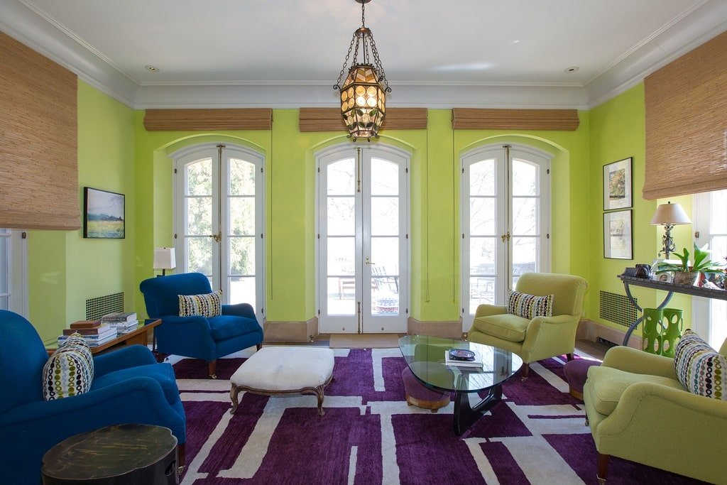 This other living room has a bright green tone to its walls adorned with tall arched windows. This is contrasted by the maroon patterned area rug paired with a couple of green and blue armchairs surrounding coffee tables. Image courtesy of Toptenrealestatedeals.com.