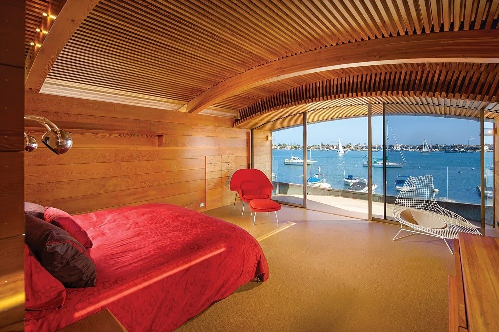 The bedroom has a wooden cove ceiling that matches well with the walls and flooring. These make the red vibrant sheets of the bed stand out. Image courtesy of Toptenrealestatedeals.com.