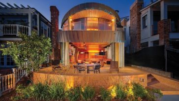 This is the front view of the house with a design that looks like an open-mouthed whale. The are open walls that combine the outdoor and indoor. You can also see here the elevated patio surrounded by landscaping. Image courtesy of Toptenrealestatedeals.com.