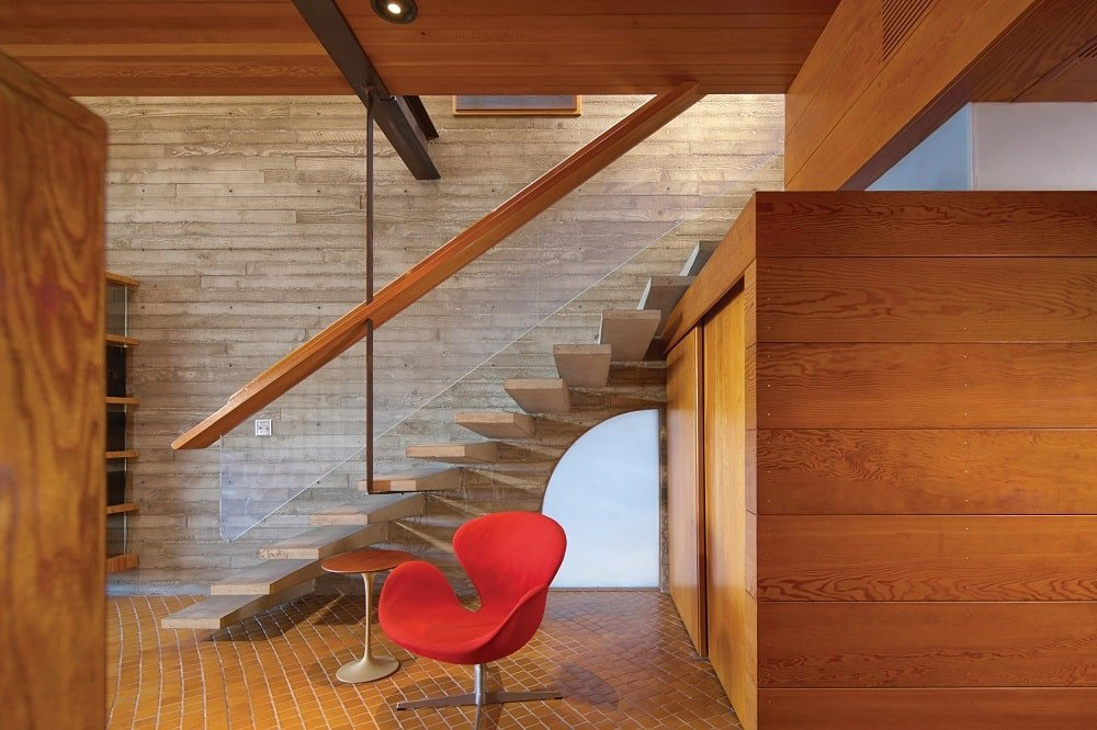 This is the set of stairs a few steps from the living room area. Here you can see the unique design of glass railings that make the wooden banisters seem like floating. These matches well with the surrounding wooden structures. Image courtesy of Toptenrealestatedeals.com.