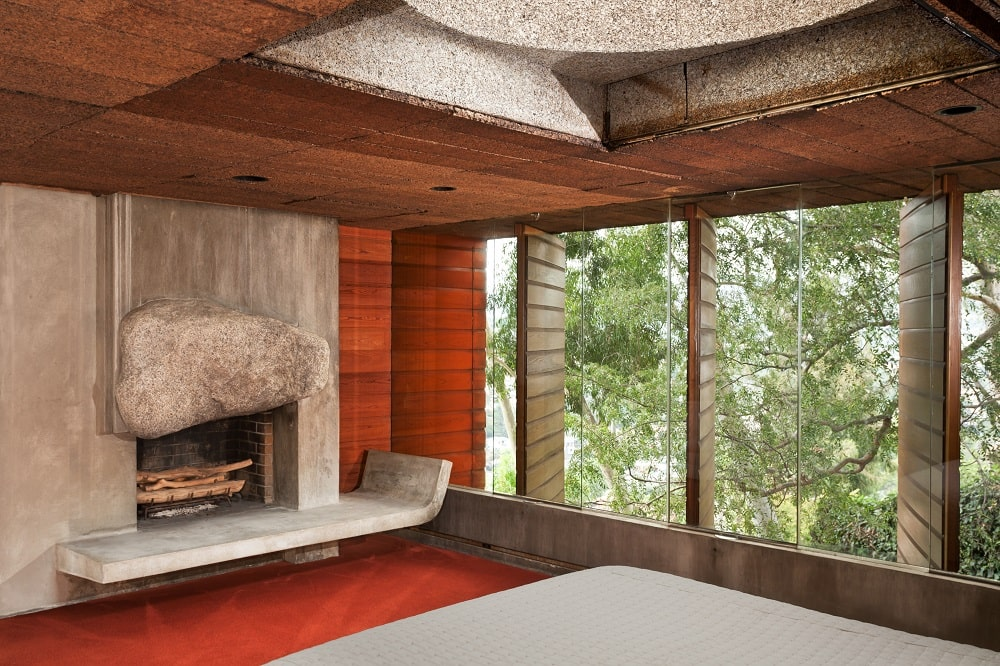 This is the bedroom with swiveling wooden windows on the side and a large concrete fireplace across from the bed. Image courtesy of Toptenrealestatedeals.com.