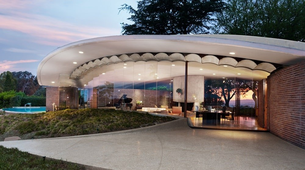This an exterior view of the house with glass walls, a dome concrete roof and a glimpse of the interior that has recessed lights and various concrete structures. Image courtesy of Toptenrealestatedeals.com.