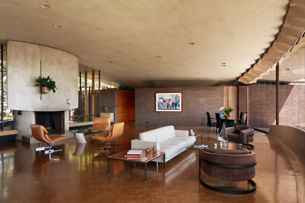 This is the spacious living room with a white sofa that stands outa gainst the dark hardwood flooring. On the far side is a large concrete structure that houses the fireplace. Image courtesy of Toptenrealestatedeals.com.
