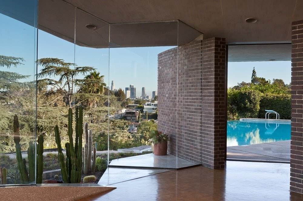 This is a view out the glass wall of the house adorned with a cactus garden just outside the glass wall and a view of the pool on the far side. Image courtesy of Toptenrealestatedeals.com.