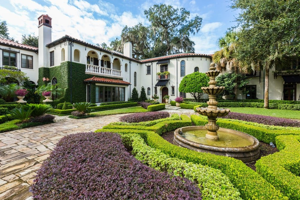 This is a look at the front of the house with bright white exterior walls adorned by the colorful shrubs, tall trees and a large fountain surrounded by low hedges. Image courtesy of Toptenrealestatedeals.com.