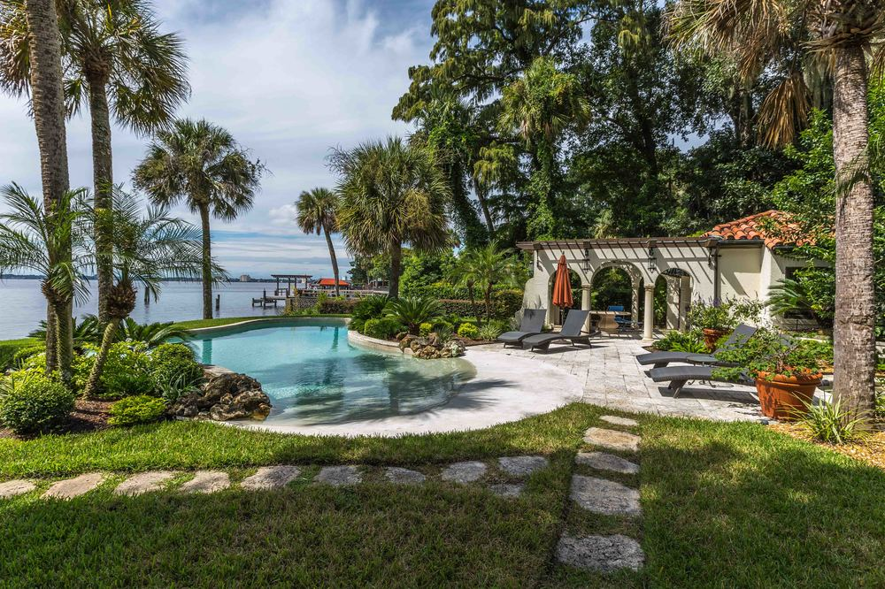 This is a look at the backyard pool adorned with the surrounding landscape of tropical trees and grass lawns with concrete walkways. Image courtesy of Toptenrealestatedeals.com.