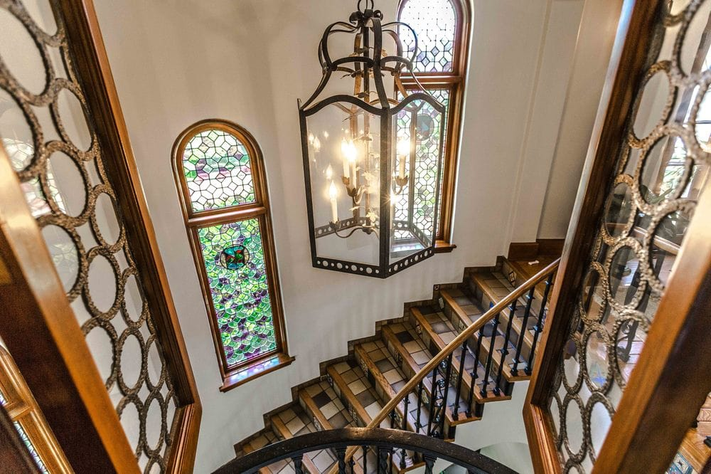 This is a look at the space above the foyer adorned with a large lantern pendant light. You can see here the curved staircase with wooden steps and a couple of tall arched windows. Image courtesy of Toptenrealestatedeals.com.