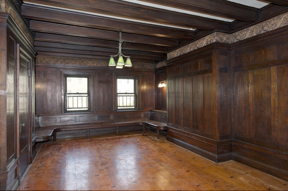 The billiards room has a beamed ceiling that hangs a small chandelier in the middle for the pool table. You can also see here the hardwood flooring that complements the darker wooden walls. Image courtesy of Toptenrealestatedeals.com.