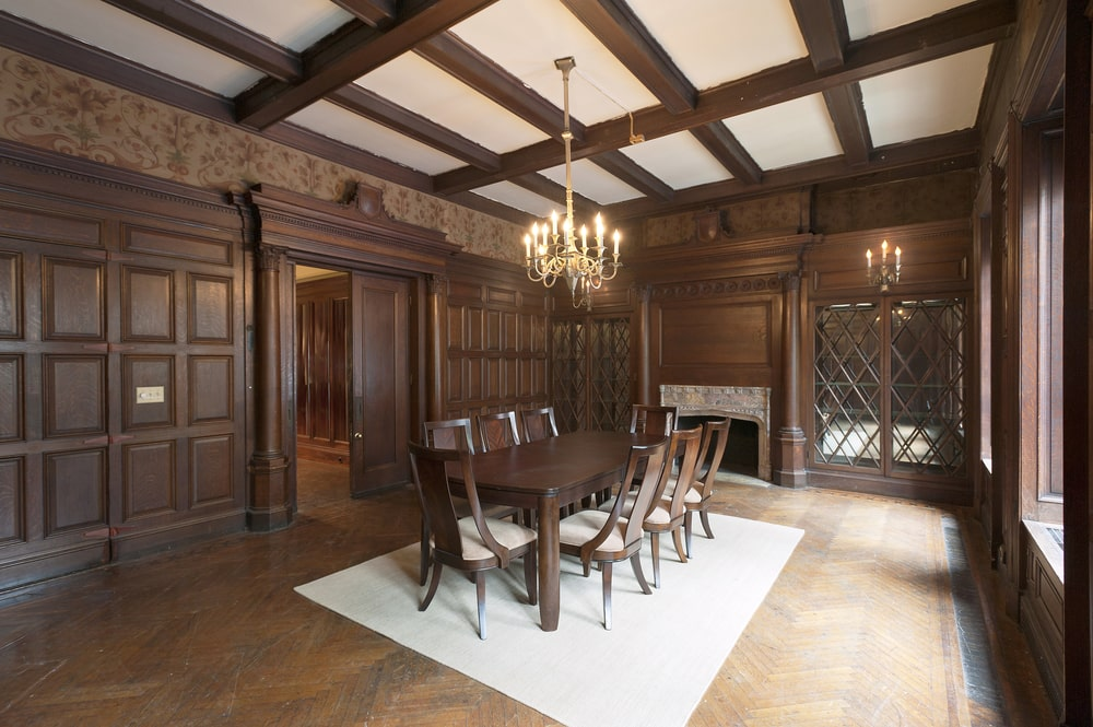 This formal dining room has a tall ceiling with dark wooden beams that match the walls and hardwood flooring. This also matches with the dining set warmed by the large fireplace on the far wall. Image courtesy of Toptenrealestatedeals.com.
