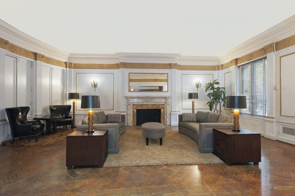 This is the family room that also serves as a sitting room with a couple of gray sofas flanking a gray ottoman across from the fireplace with a beige mantle. Image courtesy of Toptenrealestatedeals.com.
