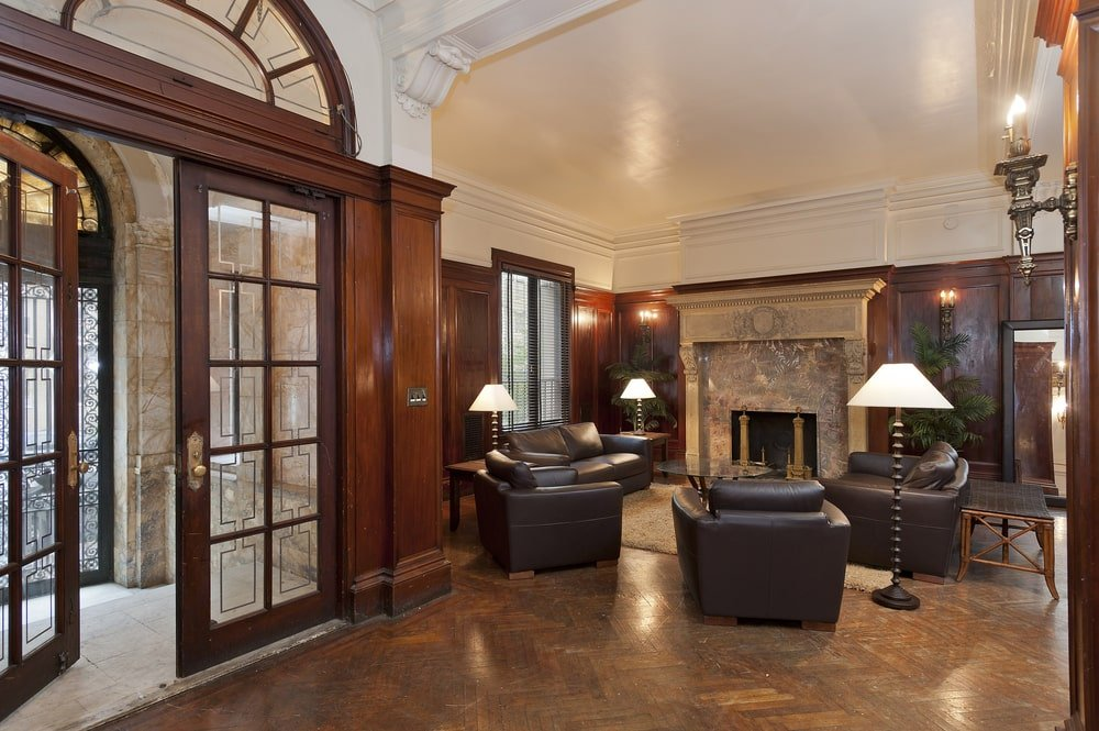 A few steps from the foyer is this living room through a set of French doors. This living room has black leather armchairs and sofa warmed by the fireplace on the far wall. Image courtesy of Toptenrealestatedeals.com.