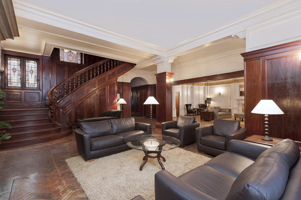 This other view of the living room shows the dark wooden staircase on the far side that blends well with the walls and the flooring. On side of this is a small arched entryway to another section of the house. Image courtesy of Toptenrealestatedeals.com.