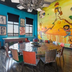Focused look at the large round table set surrounded by the blue walls and artistic wall on the side. Image courtesy of Toptenrealestatedeals.com.