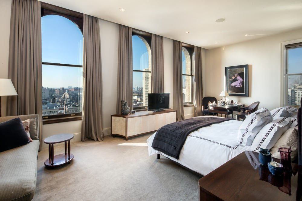 The bedroom has a white bed complemented by the surrounding beige walls, ceiling and the row of tall windows across from the bed that bring in natural lights. Image courtesy of Toptenrealestatedeals.com.
