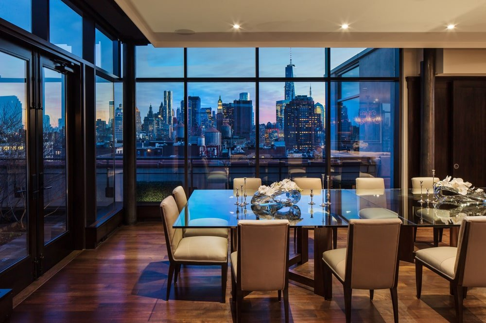 The dining are has a large glass dining table surronded by cushioned beige chairs that match the ceiling. Image courtesy of Toptenrealestatedeals.com.