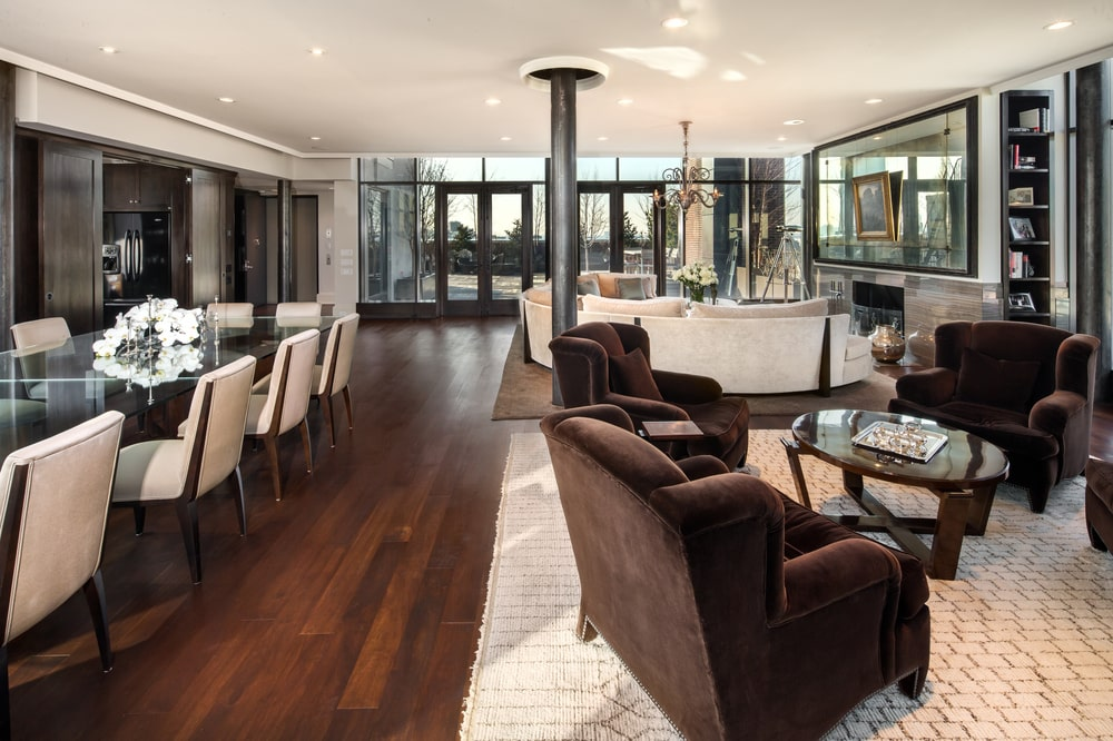 This is a look at the great room of the penthouse. Here you can see the dining area, living room and the family room areas complemented by the glass walls that give a view of the surrounding skyline of the city. Image courtesy of Toptenrealestatedeals.com.