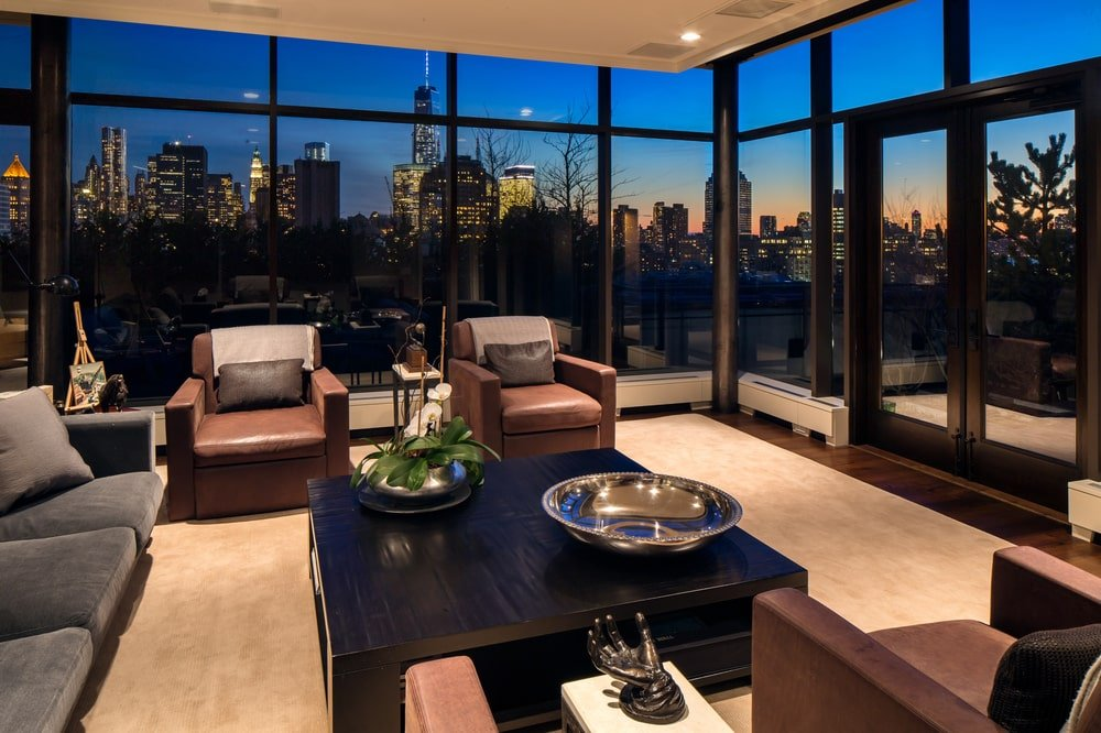 This is a nighttime view of the living room showcasing the city skyline views afforded by the surrounding glass walls. Image courtesy of Toptenrealestatedeals.com.