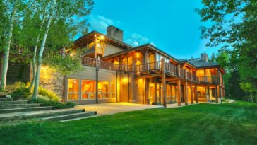This is a back view of the house showcasing the abundant glass walls, log beams, a large balcony and warm glow of the interiors matching the outdoor lights. These are then complemented by the surrounding lush landscape. Image courtesy of Toptenrealestatedeals.com.