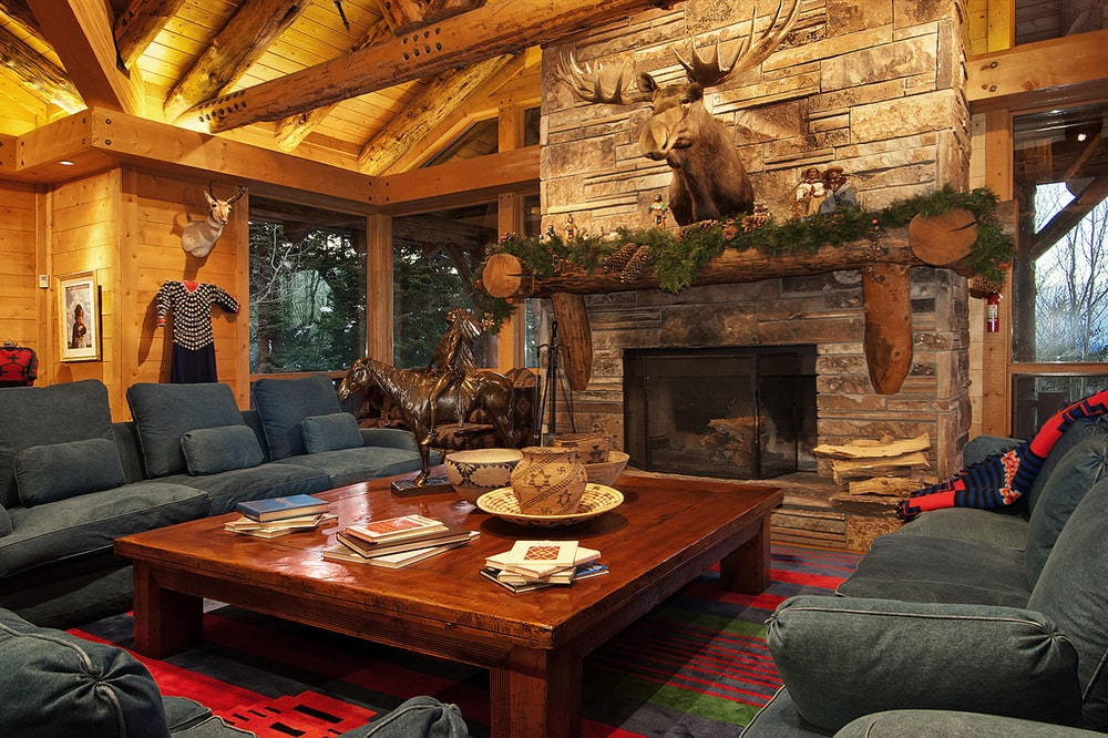 This is the spacious living room of the house with a tall wooden cathedral ceiling, a large fireplace and a wooden coffee table surrounded by a gray sofa set. Image courtesy of Toptenrealestatedeals.com.
