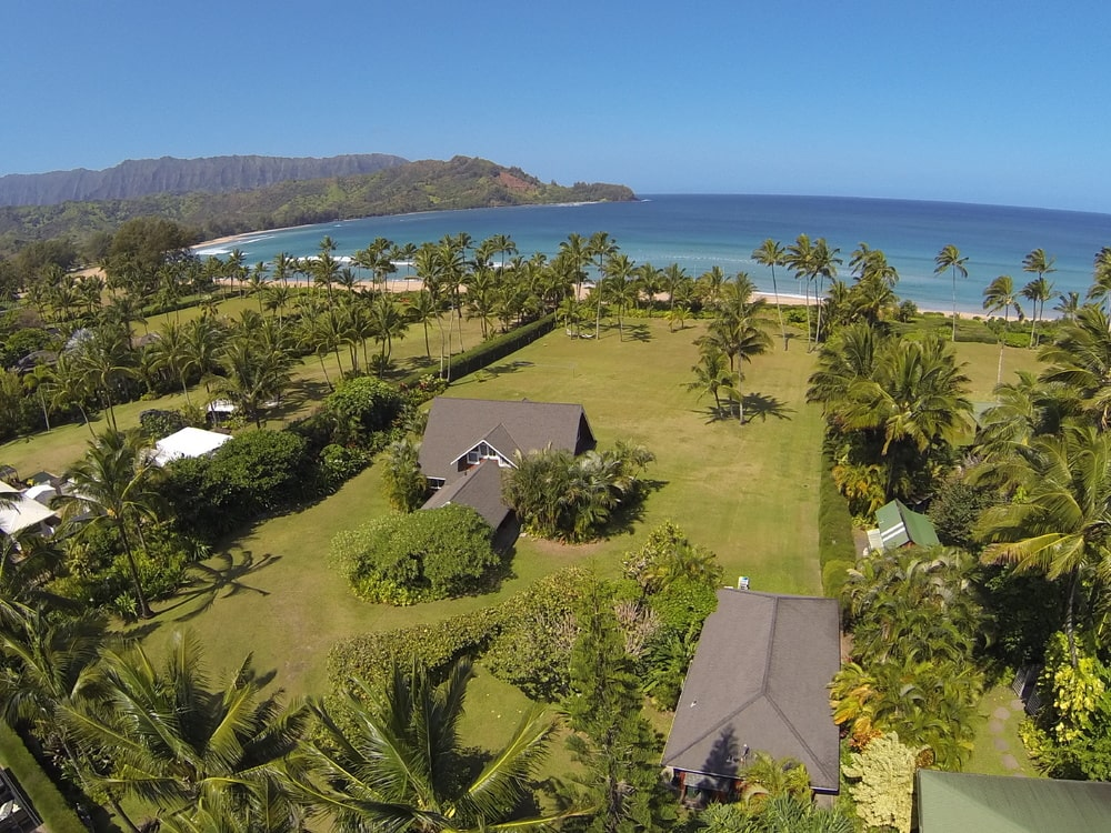 This is an aerial view of the beach house. You can see here that it is surrounded by lush landscaping of grass lawns and tall trees leading to the beach on the far end. Image courtesy of Toptenrealestatedeals.com.