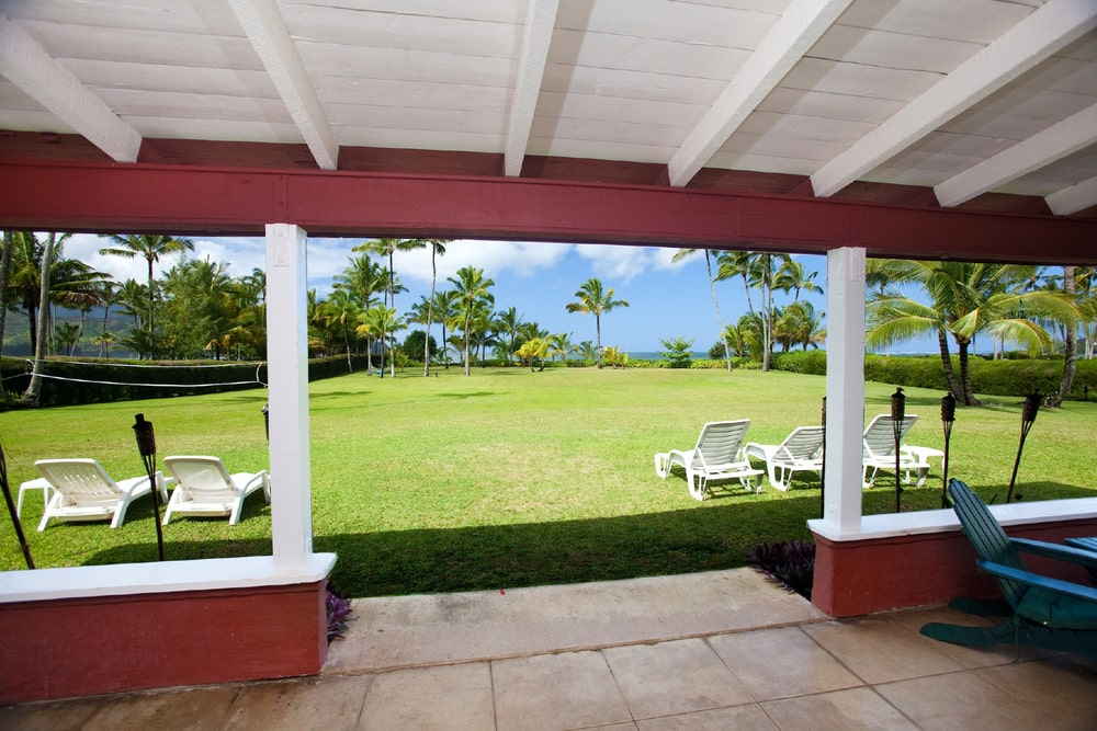 This is a view of the surrounding green landscape from the vantage of the covered patio that has a white wooden ceiling with exposed beams. A few steps a way is a set of lounge chairs on the grass lawn. Image courtesy of Toptenrealestatedeals.com.