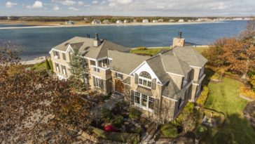 This is an aerial view of the large oceanfront house with beige exterior walls adorned by the multiple glass windows and white accent. Image courtesy of Toptenrealestatedeals.com.