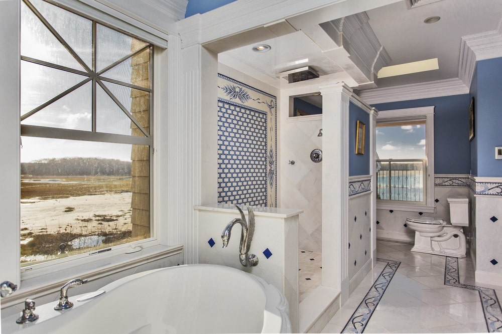 The bathroom has a bathtub that is placed under the large window with a view of the beach. Image courtesy of Toptenrealestatedeals.com.