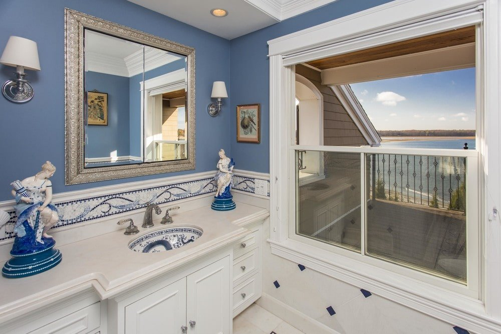 This other view of the bathroom shows the vanity topped with a large wall-mounted mirror that stands out against the gray upper walls. Image courtesy of Toptenrealestatedeals.com.