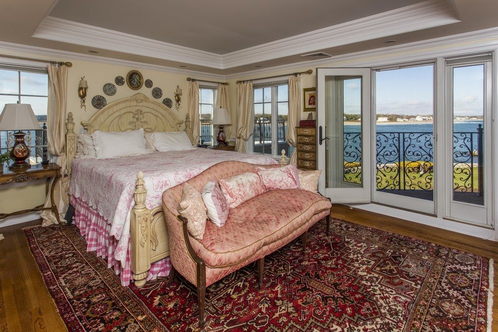 The bedroom has a large beige bed with a beige headboard that blends with the walls. This is contrasted by the red patterned area rug on the floor. Image courtesy of Toptenrealestatedeals.com.