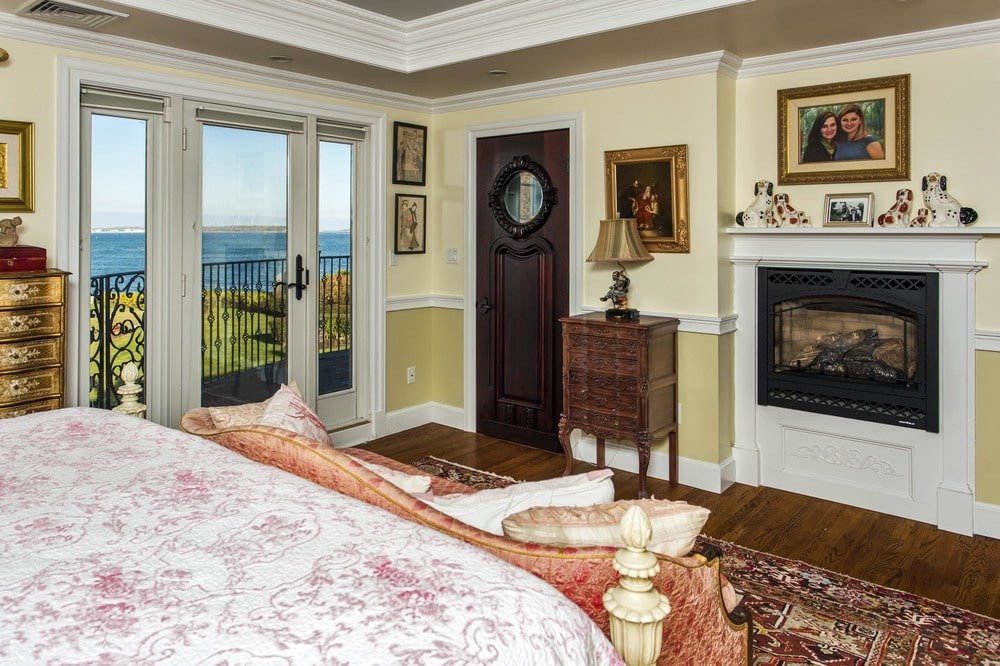 This other view of the bedroom shows the fireplace across from the bed with a white mantle topped by a painting. Image courtesy of Toptenrealestatedeals.com.