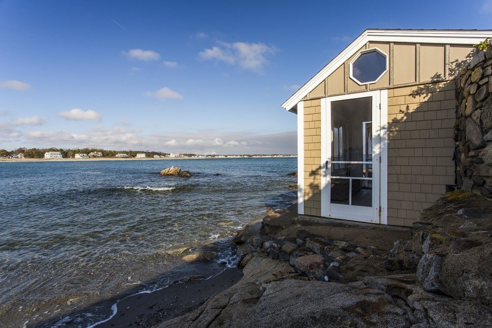 A few steps from the edge of the backyard lawn is this oceanside cottage that is built right on the beach. Image courtesy of Toptenrealestatedeals.com.