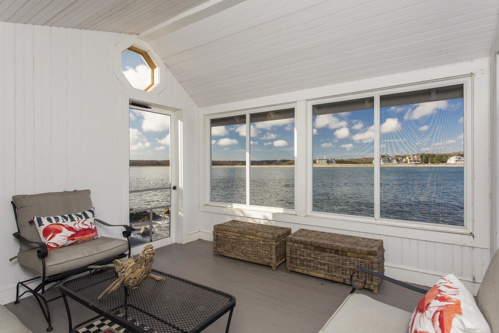 This other view of the cottage interio shows the glass door and the glass windows facing the ocean. Image courtesy of Toptenrealestatedeals.com.