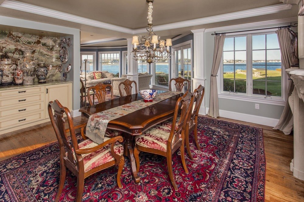 The formal dining room has a large wooden dining table topped with a simple chandelier. Image courtesy of Toptenrealestatedeals.com.