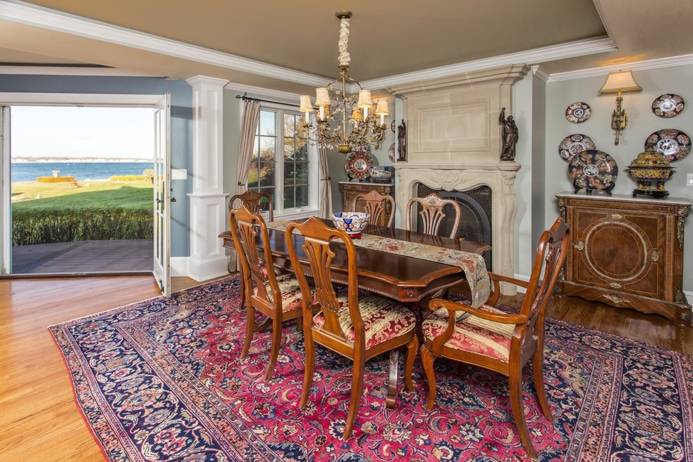 This other view of the dining room shows the fireplace on the far side with a beige mantle that blends with the ceiling. Image courtesy of Toptenrealestatedeals.com.