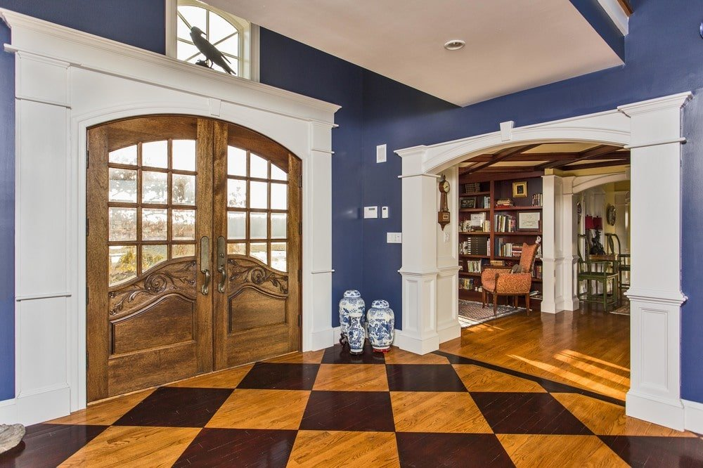 Upon entry of the house, you are welcomed by this foyer that has a checkered pattern to its hardwood flooring contrasted by the gray walls and white molding. Image courtesy of Toptenrealestatedeals.com.