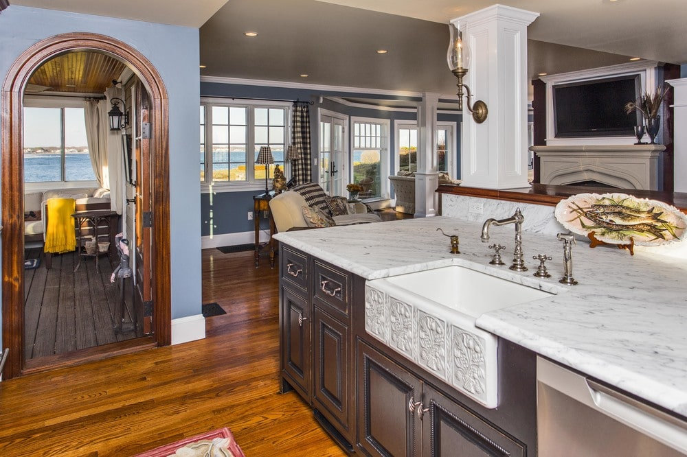 This is a close look at the kitchen island with a dark wooden cabinetry that is contrasted by the white marble countertop and the white pillar. Image courtesy of Toptenrealestatedeals.com.