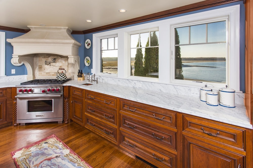This closer look at the kitchen shows the cooking area on the far side with a stainless steel oven that stands out against the wood tones of the cabinetry and floor. Image courtesy of Toptenrealestatedeals.com.