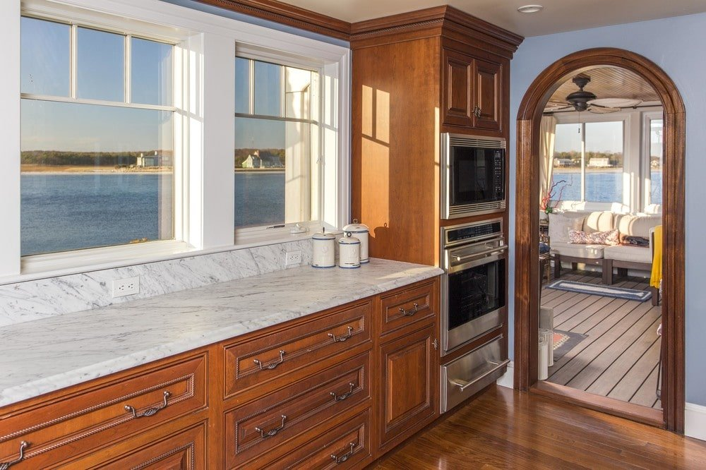 This other view of the kitchen shows the stainless steel appliances that stand out against the dark wooden cabinetry that matches the floor. Image courtesy of Toptenrealestatedeals.com.
