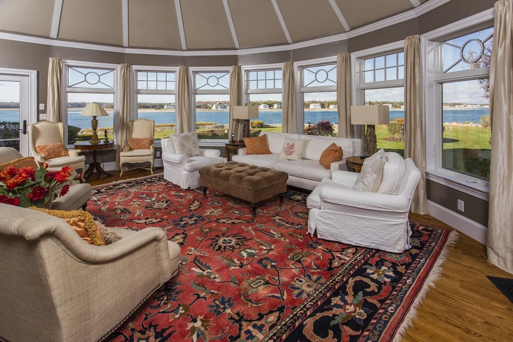 The living room has bright white slipcovers on the sofa set that is brightened by the surrounding row of windows. Image courtesy of Toptenrealestatedeals.com.