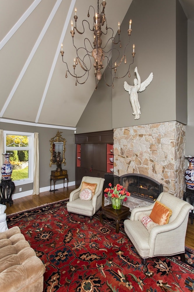This is a look at the large stone fireplace of the living room topped with a tall cathedral ceiling and a wall-mounted statuette. Image courtesy of Toptenrealestatedeals.com.