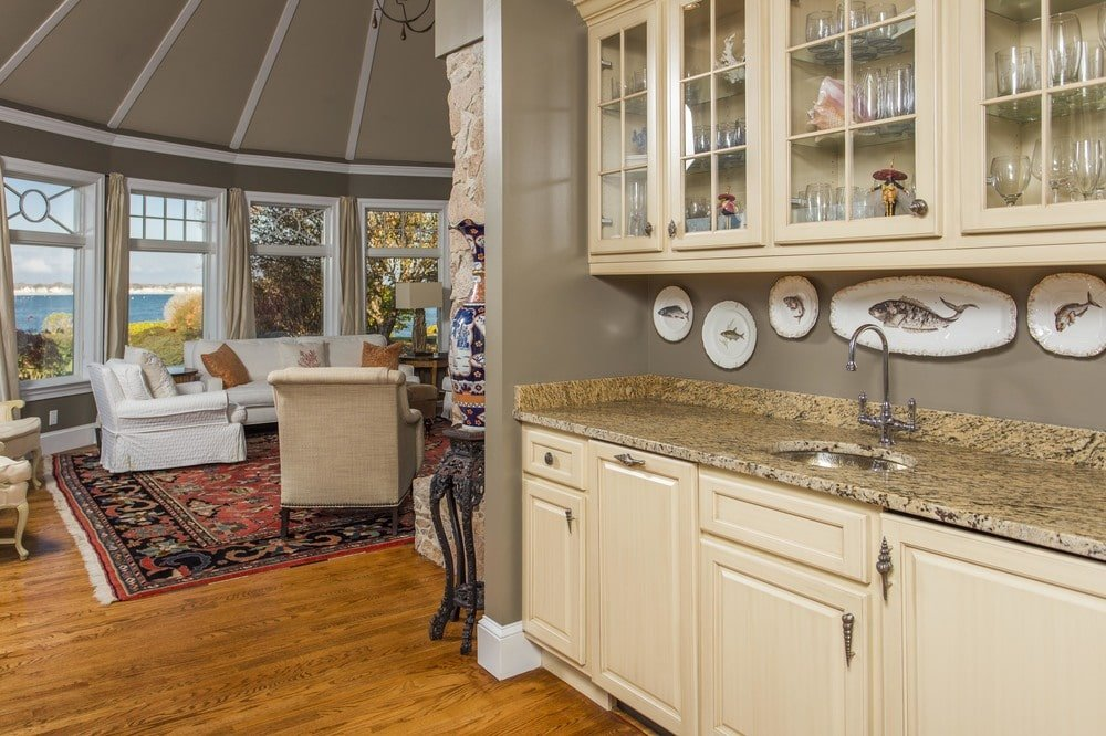 A few steps from the living room is the edge of the kitchen with a built-in beige cupboard with its own sink. Image courtesy of Toptenrealestatedeals.com.