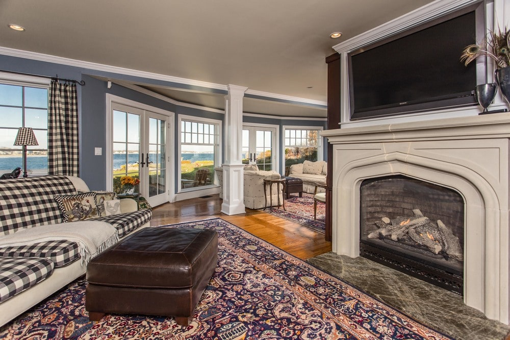 A few steps from the main living room is this other living room area with a sofa facing its own fireplace that is topped with a TV. Image courtesy of Toptenrealestatedeals.com.