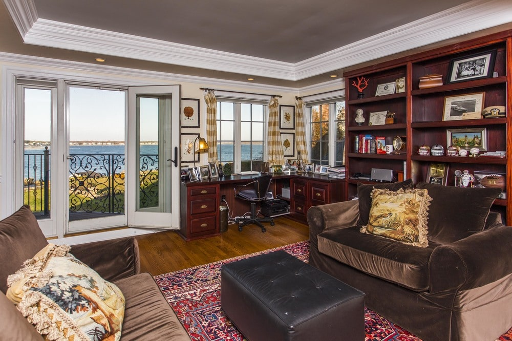 The home office has a built-in dark wooden desk at the far corner under the windows. This is attached to a dark wooden bookshelf on the side. Image courtesy of Toptenrealestatedeals.com.