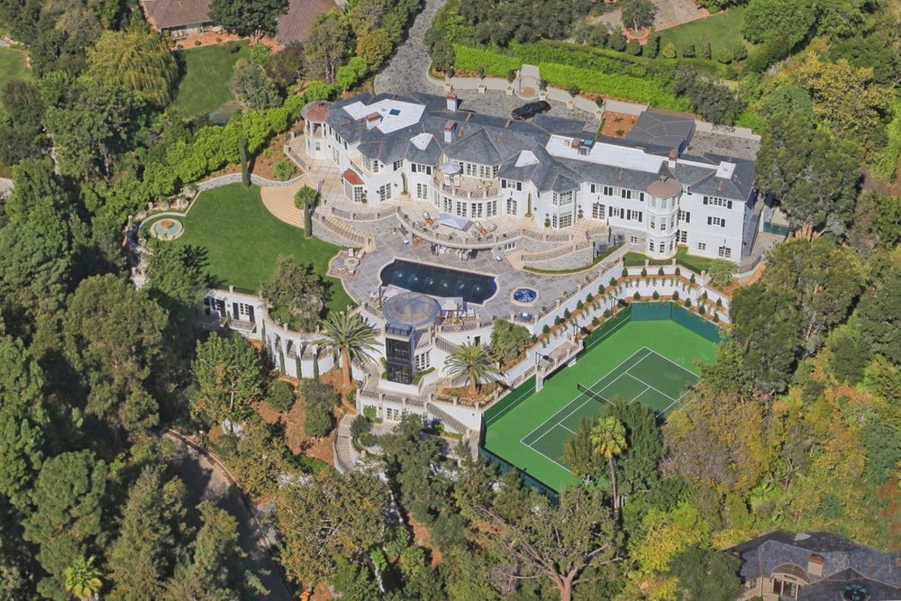 This is an aerial view of the whole estate showing the massive main house with a pool and a tennis court on the side. These are all complemented by the landscape that is filled with trees and grass lawns. Image courtesy of Toptenrealestatedeals.com.