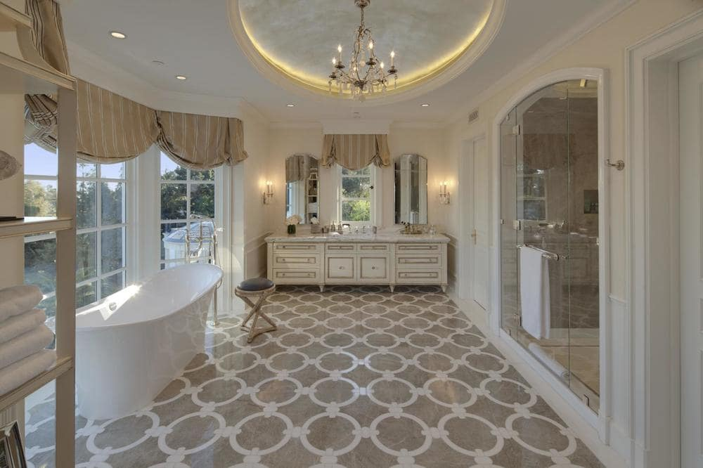 The bathroom has a patterned set of flooring tiles, a freestanding bathtub by the windows and an arched entryway for the glass-enclosed shower area. Image courtesy of Toptenrealestatedeals.com.