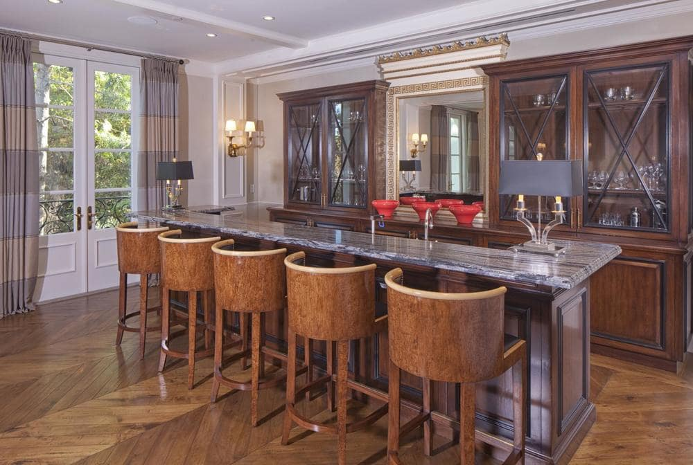 The wet bar of the house has a set of brown stools paired with the tall bar across from the dark wooden cabinetry. Image courtesy of Toptenrealestatedeals.com.