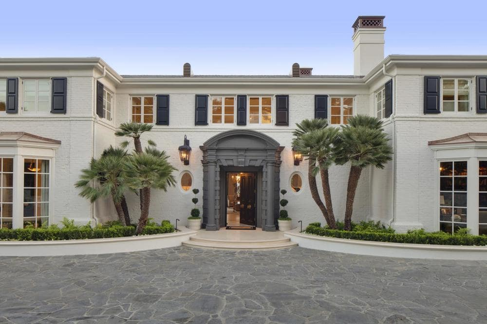 This is a front view of the house showcasing the main entrance of the house that is flanked with medium-sized trees on planters that run along the exterior walls. Image courtesy of Toptenrealestatedeals.com.