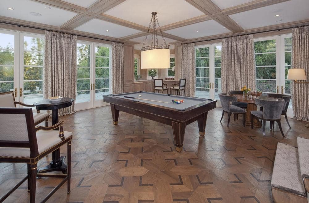 This is the spacious game room with a large pool table in the middle. It has beige coffers on its ceiling that blends well with the curtains of the surrounding glass walls. Image courtesy of Toptenrealestatedeals.com.