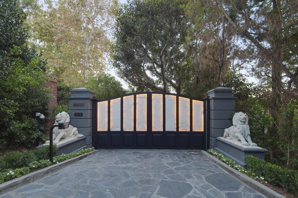 This is a look at the main gate of the estate. This is flanked with a couple of lion statues and adorned with tall trees. Image courtesy of Toptenrealestatedeals.com.