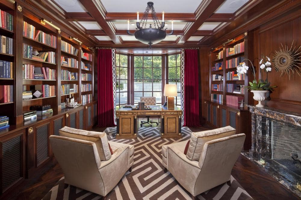 This is the library that also doubles as the home office. It has dark brown tones on its built-in wooden bookshelves that match with the hardwood flooring and the coffered ceiling. Image courtesy of Toptenrealestatedeals.com.